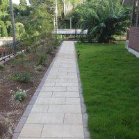 お庭への長いアプローチには透水性の方形石材を敷設