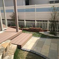 お庭に柔らか味を与える古レンガ造の曲線的な花壇と植栽の入れ替えがさらにお庭を引立てています